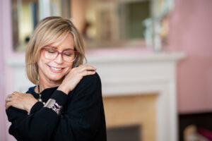 Woman in her mid fifties with glasses posing in her living room.