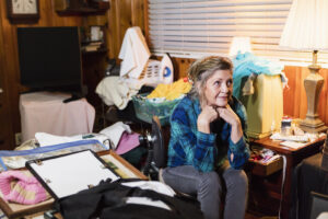 A senior woman in her 60s at home, sitting in a messy, cluttered room, looking away with a serious expression